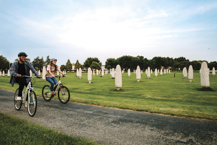 Two friends biking past the field of corn