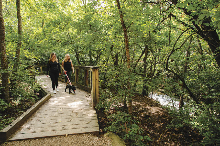 Two girls walking a dog on the path at Indian Run Falls