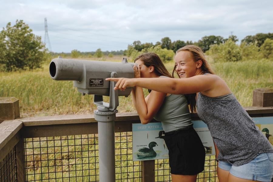 Two teenage girls looking through the telescope at Glacier Ridge Wetlands