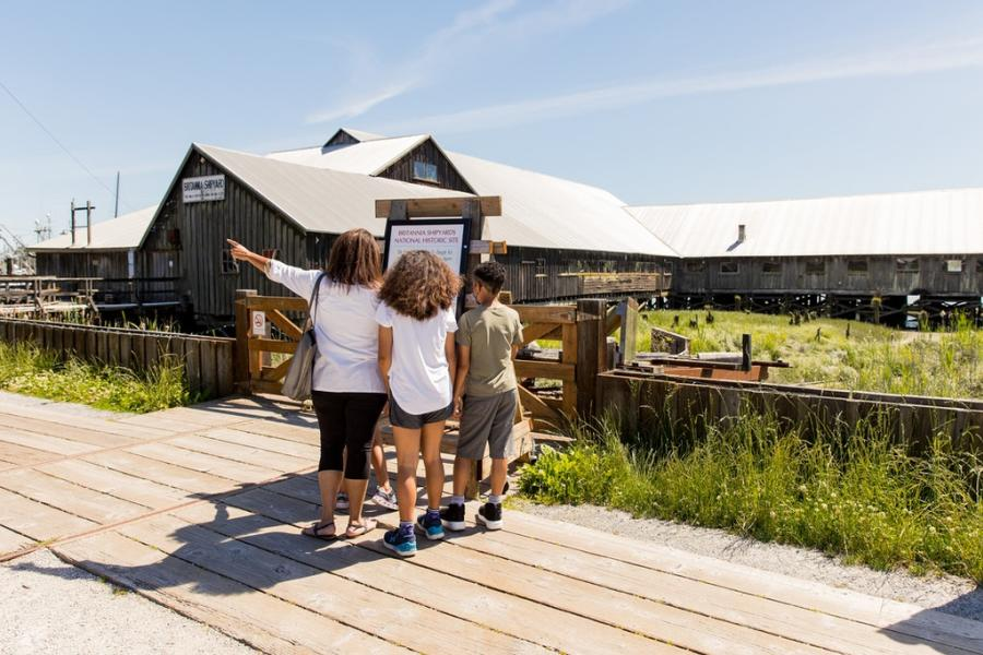 A family of four looks at a sign outside the Britannia Shipyards in Richmond, British Columbia
