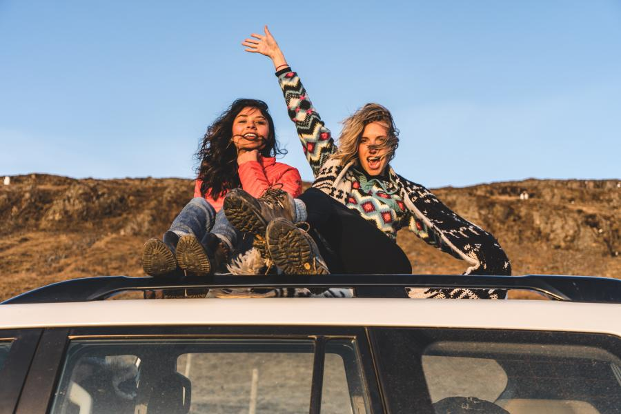 Girls-waving-on-top-of-a-car-during-road-trip