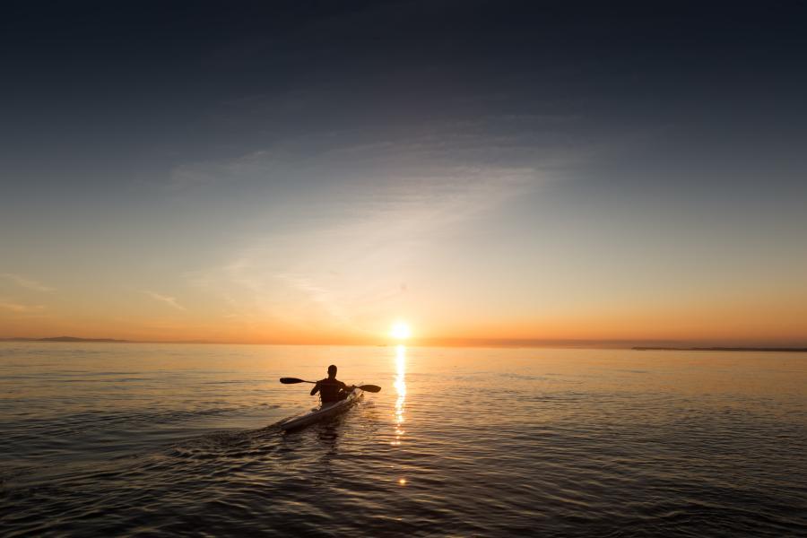 Man-kayaking-on-the-bay-during-the-sunset