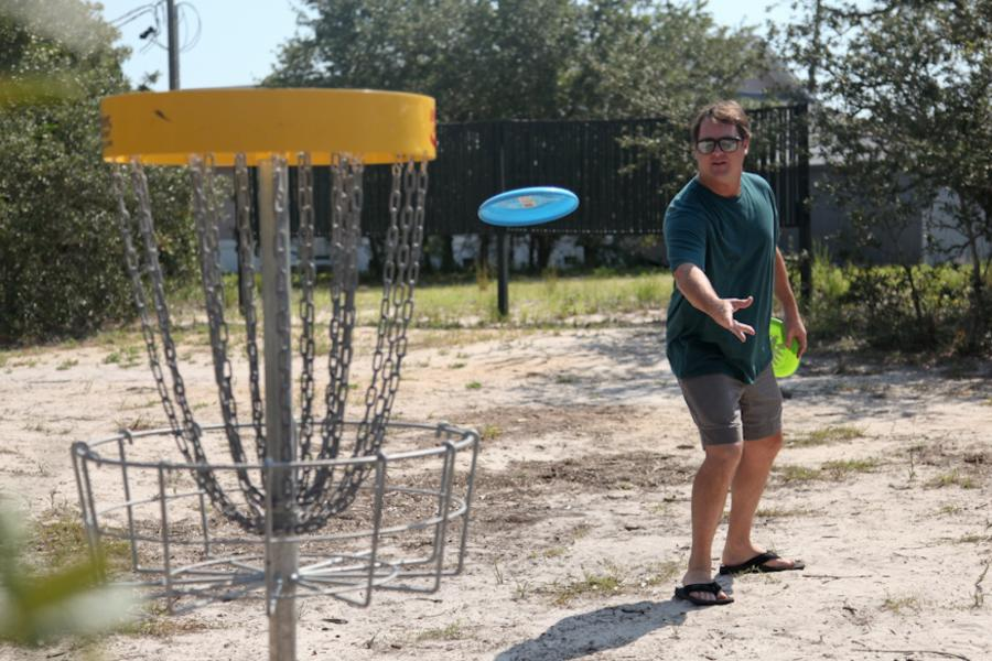 Man throws frisbee at disc golf goal