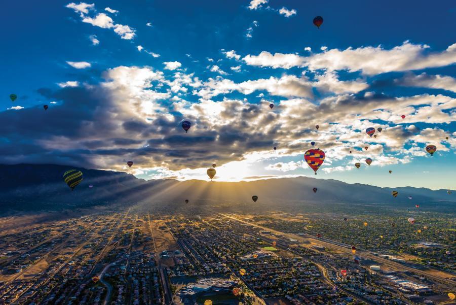 balloons and sun rising over sandia mountains
