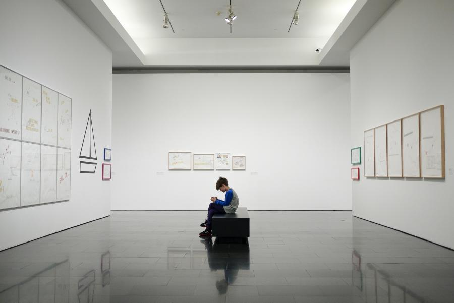 Boy-sitting-on-a-museum-bench-looking-at-his-phone