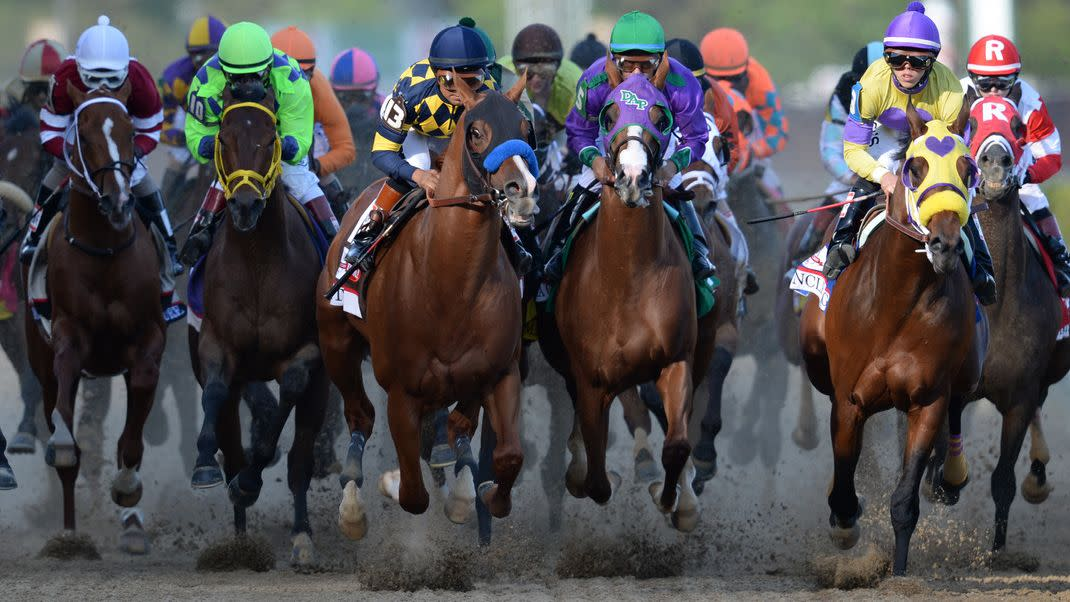 Horses and jockeys racing toward the camera at the Kentucky Derby