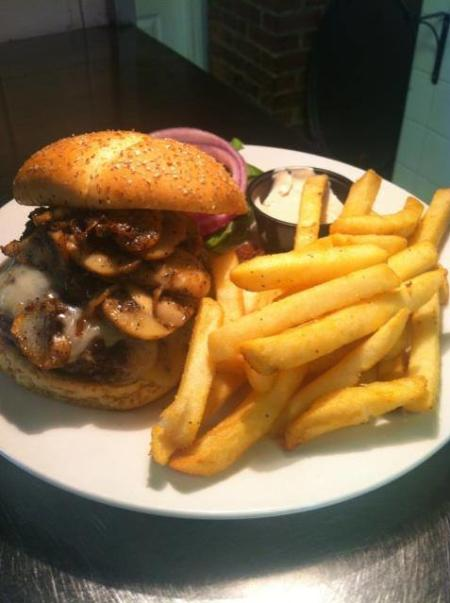 cheeseburger with mushrooms and swiss and french fries on a plate at blinkers tavern in covington ky