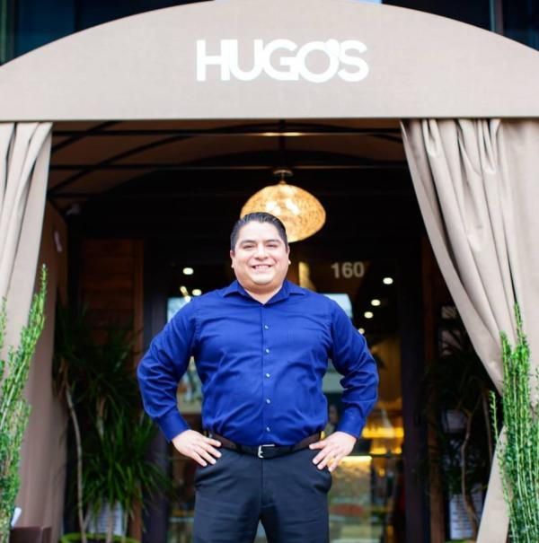 Restaurant owner, Hugo, standing proudly with his hands on his hips in front of the Hugo's restaurant