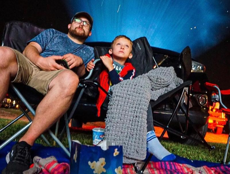 A father and son watching a movie at the Starlite Drive-In