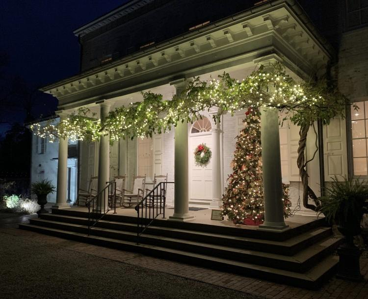The exterior of Morven Museum illuminated with holiday decor in the evening