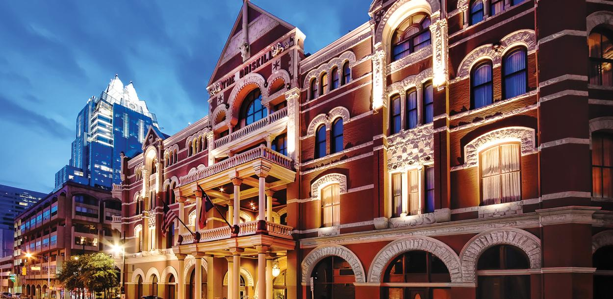 The Driskill Hotel exterior at sunset with frost bank tower behind