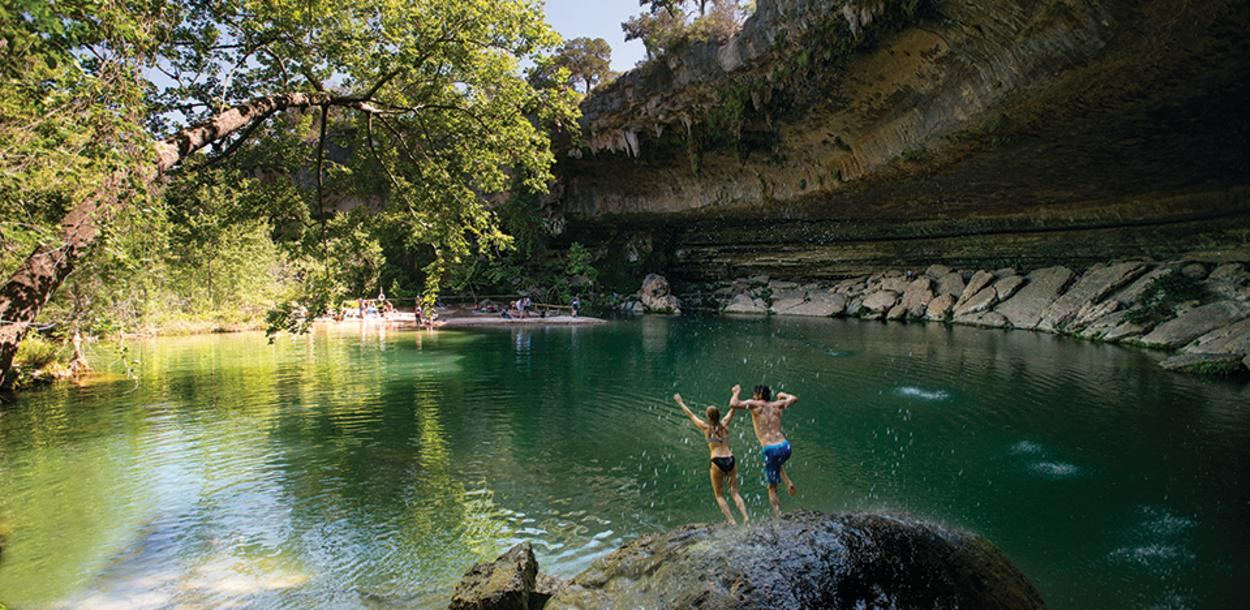 Couple jumping into Hamilton Pool