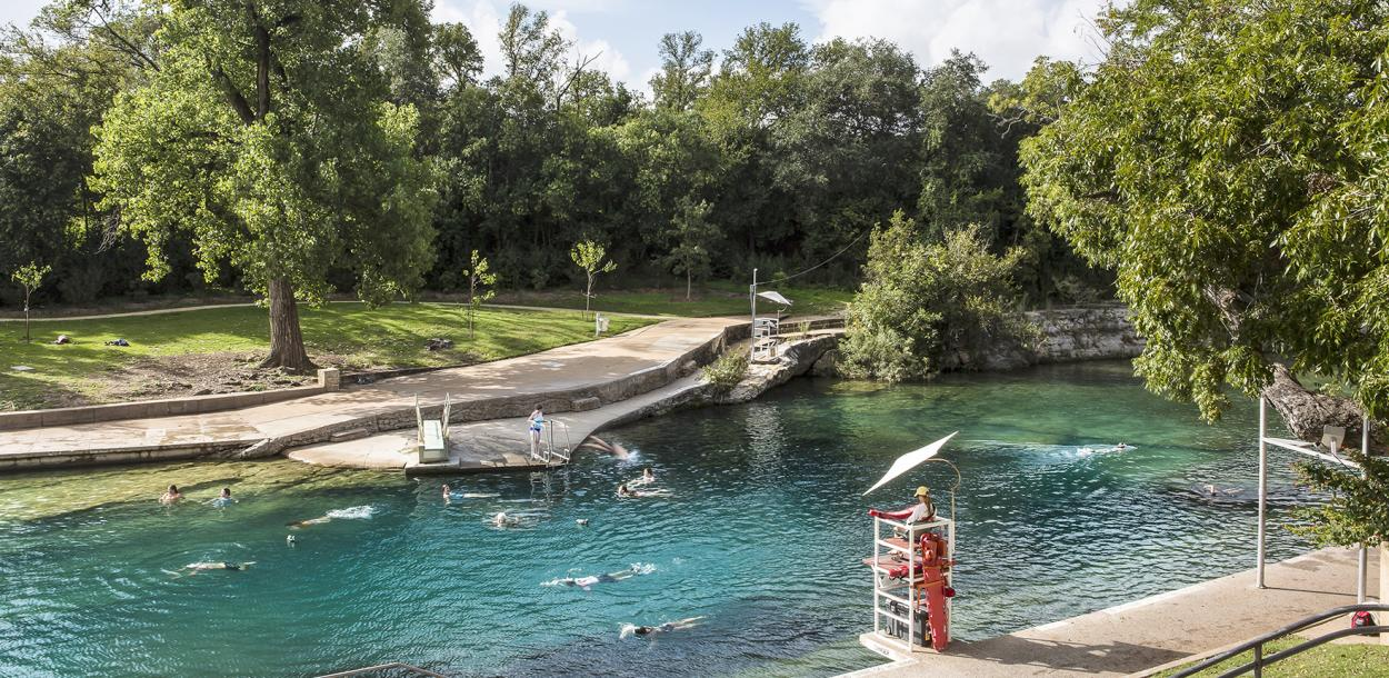 Historic Barton Springs Pool with several people swimming through the clear water and a lifeguard on duty