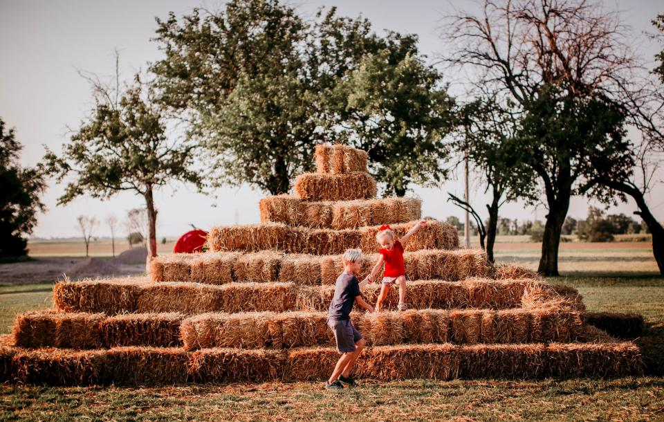 Children playing on the haystack at Cedar Creek Pumpkin Patch in Wichita
