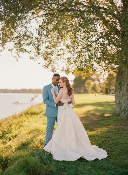 A wedding couple under a tree by the water.