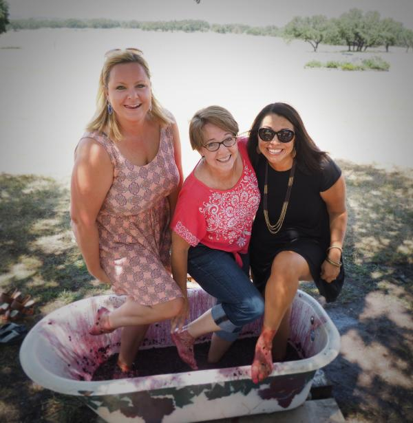 Ladies smile during a grape stomp at a winery near Fredericksburg, TX