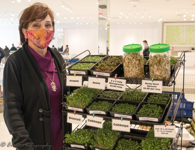 Woman showcases her crop at the Maple Grove Farmers Market