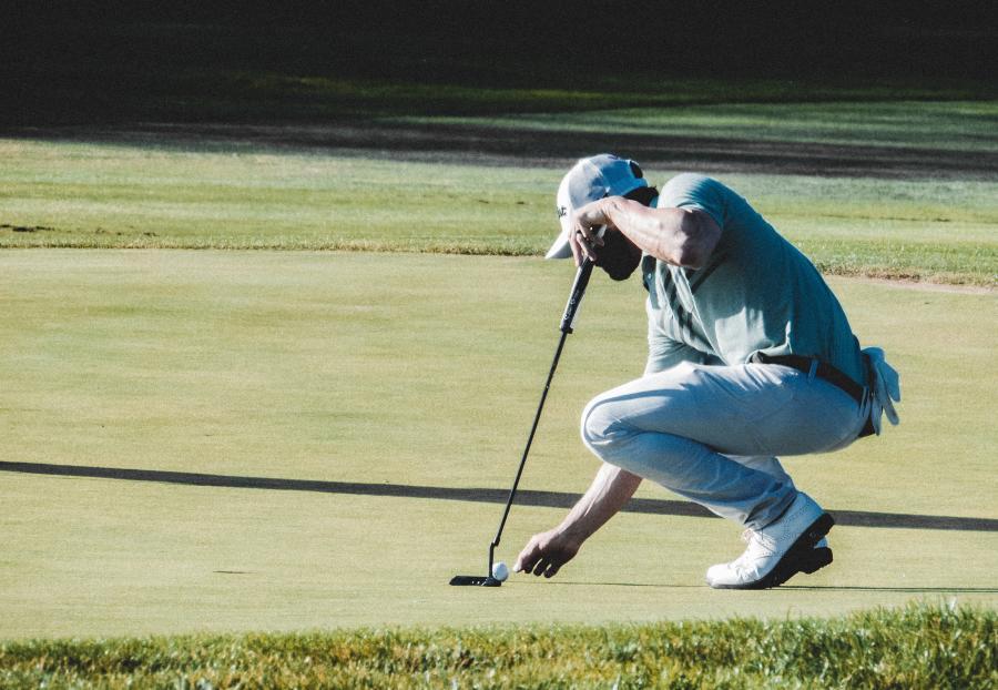 Man-placing-golf-ball-on-the-grass