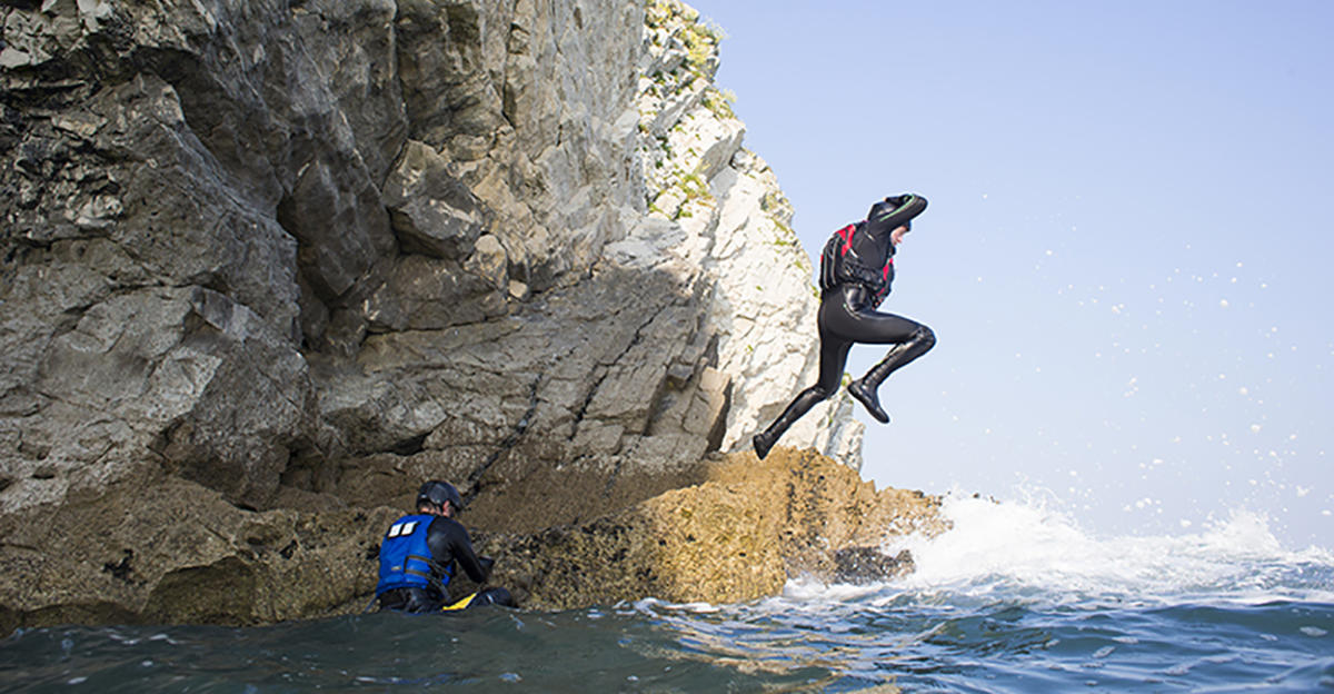 Person jumping off a rock, coasteering