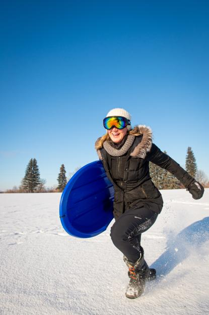 A woman gets a running start on her blue sled.