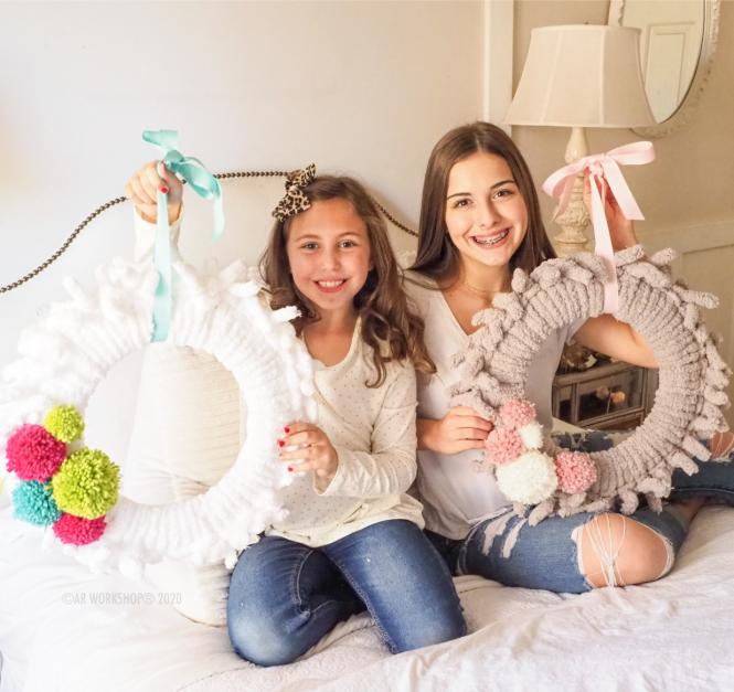 Two young girls show off their completed wreaths from the AR Workshop DIY Kits.