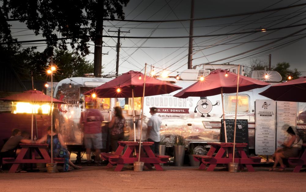 Gourdoughs donuts South First Street airstream food trailer at twilight with tables and twinkle lights