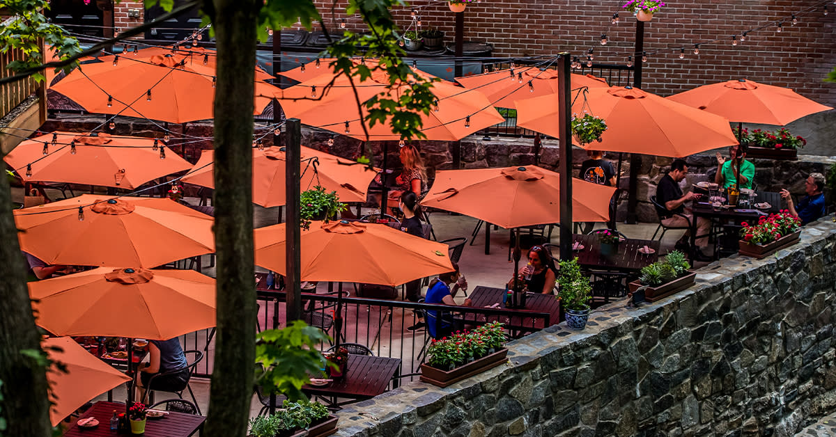 People Sitting Under Red Umbrellas On The Patio Of Umi Sushi In Ellicott City