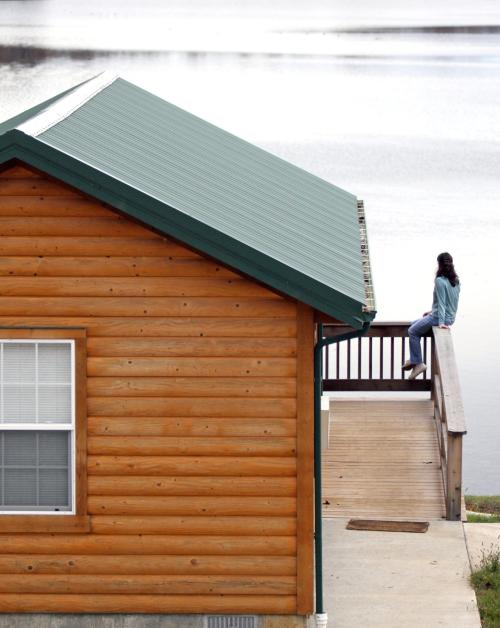 A girl sitting on a rail overlooking a lake at a Kansas State Park cabin