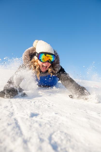 A woman enjoys sliding through the snow on a blue sled.