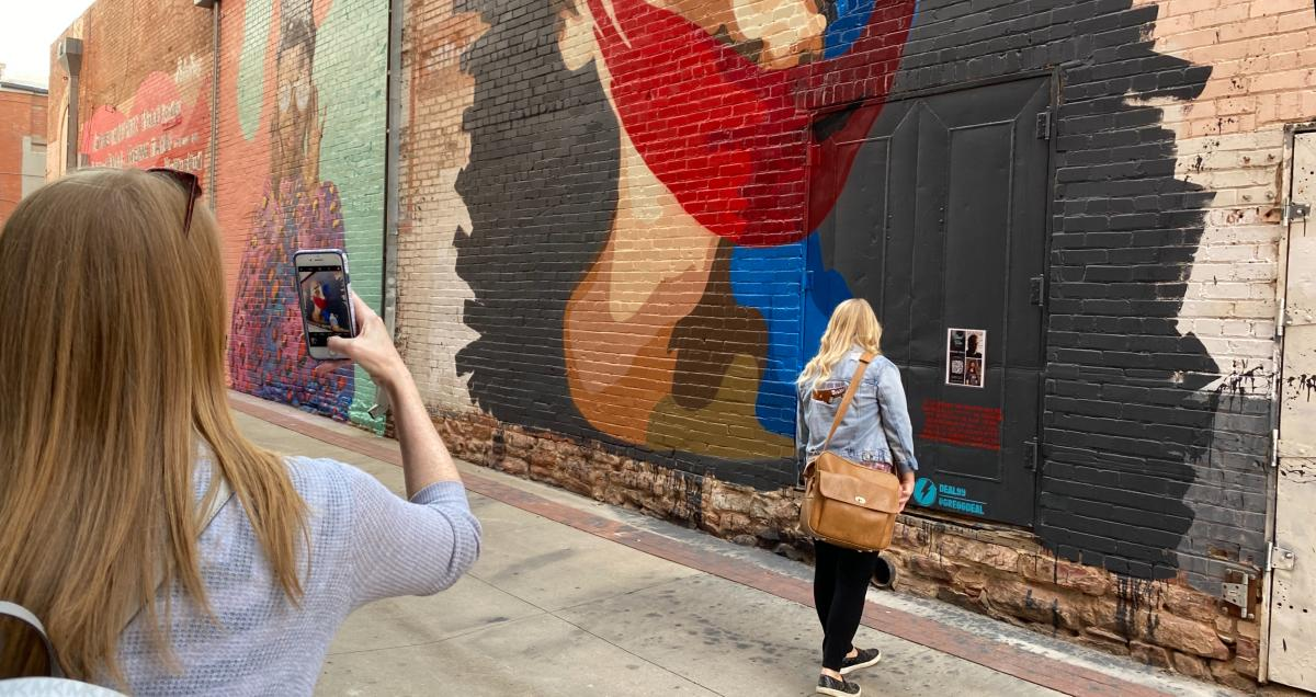 Women taking pictures of the Street Wise Murals Behind Boulder Theater