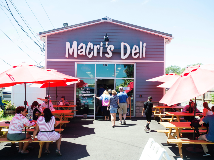 Macri's Deli exterior with people out front at picnic tables covered by umbrellas