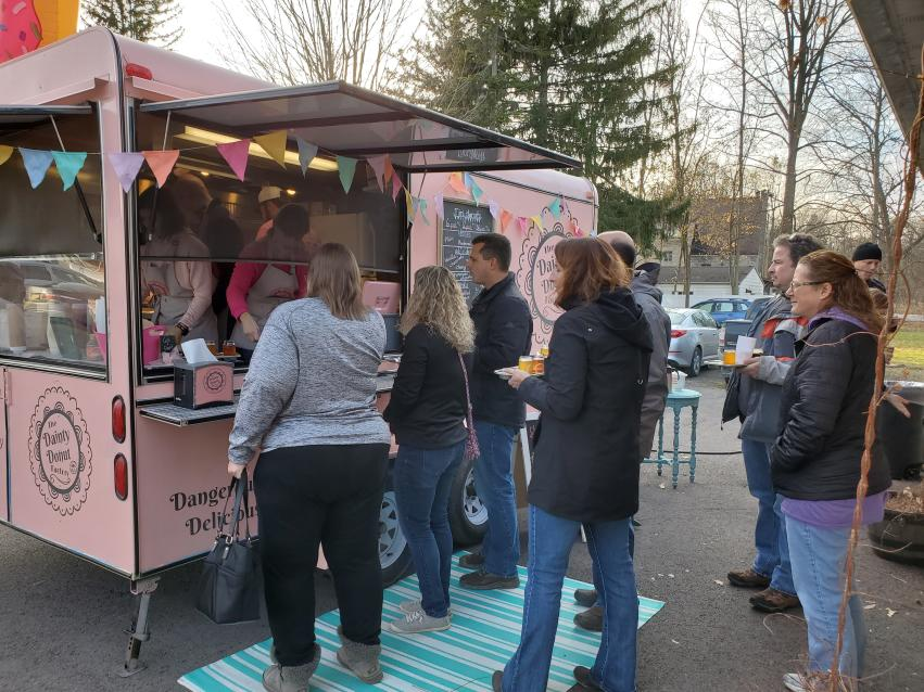 A group of people ordering and waiting outside the pink Dainty Donut food truck