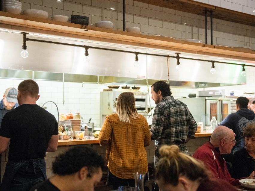 A couple sitting at a counter that overlooks the Kindred Fare kitchen operations
