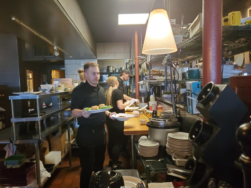 A busy kitchen scene with a server holding plates ready to go out to the tables