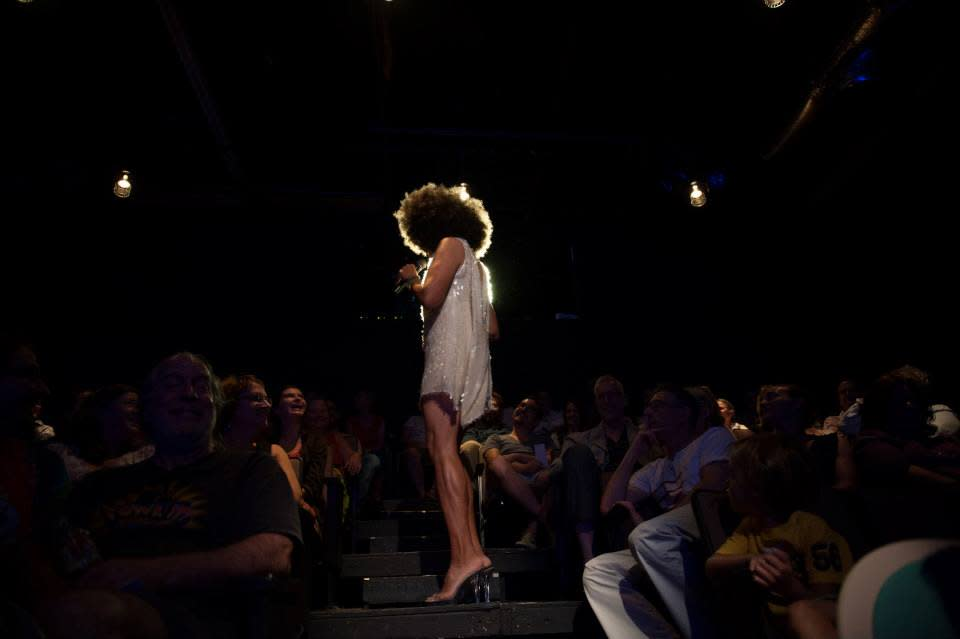 Photo showing a women performing at Salvage Vanguard Theater. She is wearing a short white dress and is standing in the center of the audience, with her back turned to the camera