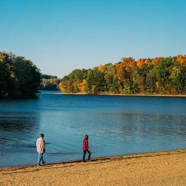 Image of two people strolling along the lake shore in fall under a bright blue sky