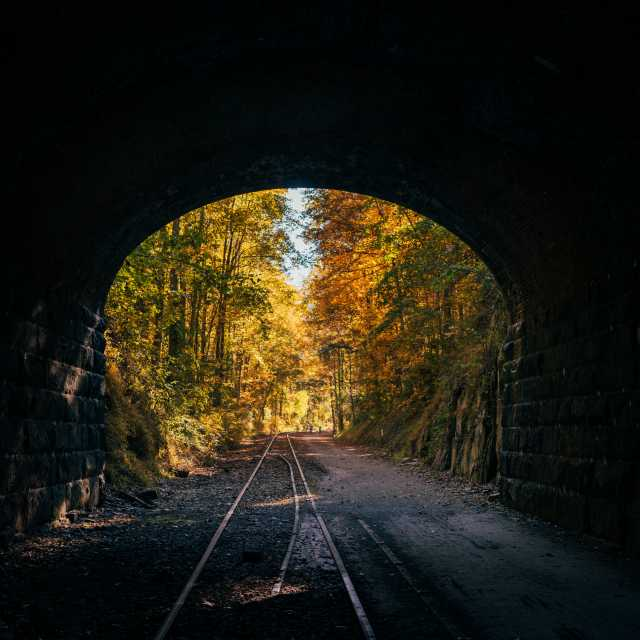 Looking out of the Howard Tunnel at the bright autumn foliage along the rail trail