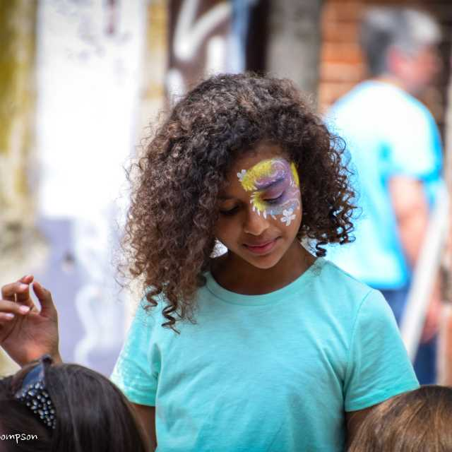 A young girl in a light blue shirt with colorful face paint
