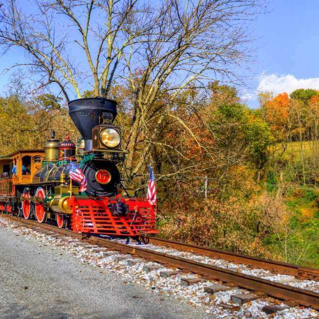 The No. 17 steam engine rolls through the valley, full of bright fall foliage