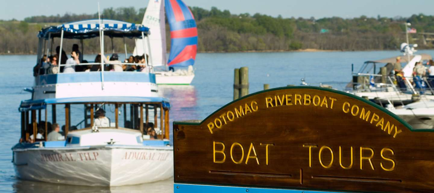 Boat Behind Boat Tours Sign On Water