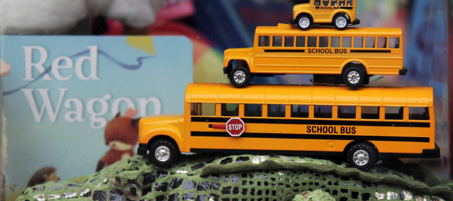 Three Small School Buses Stacked On A Toy Crocodile