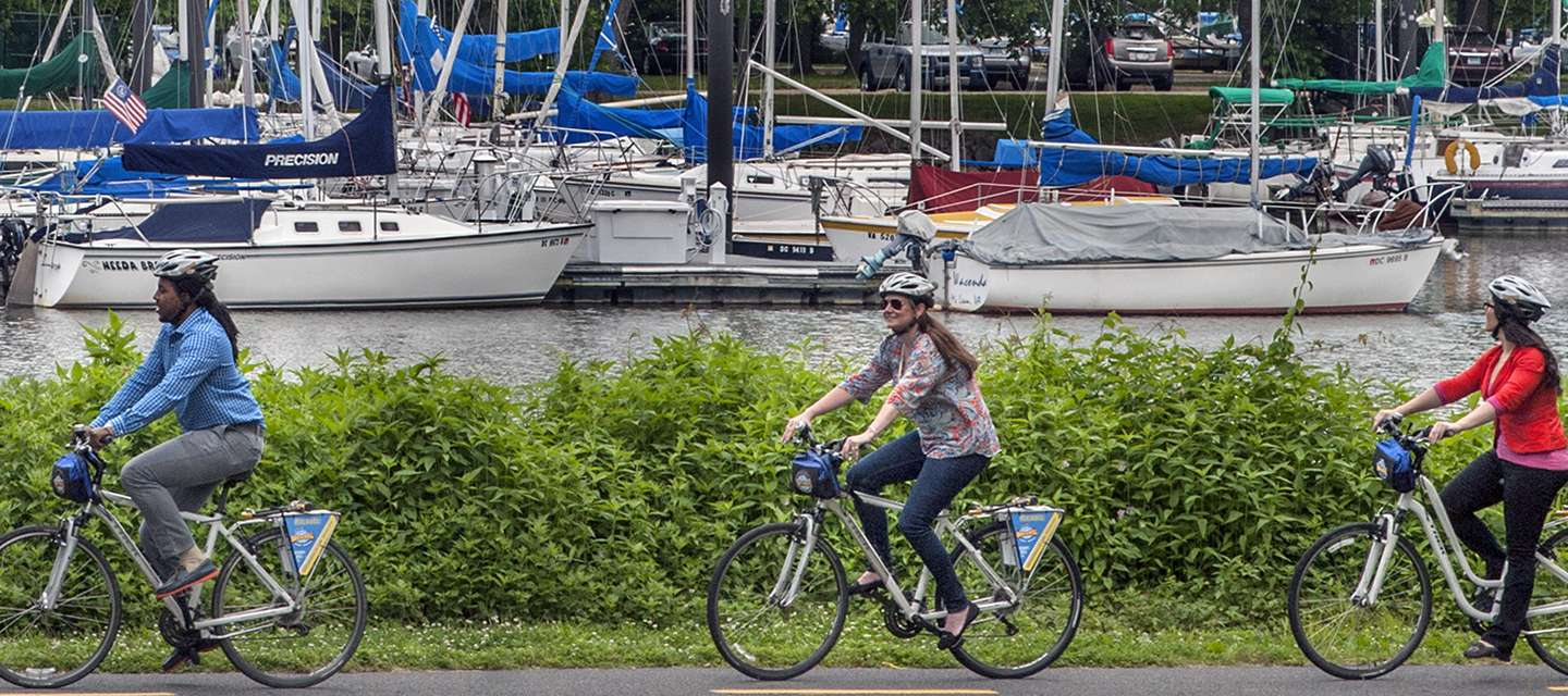 Three People Biking Past Moored Sailboats