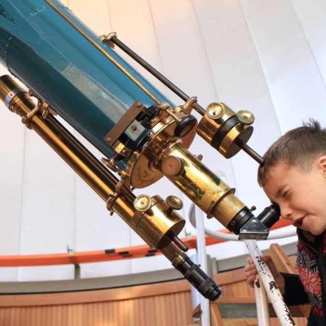 A young boy looking through a telescope at the Chabot Space & Science Center in Oakland, CA