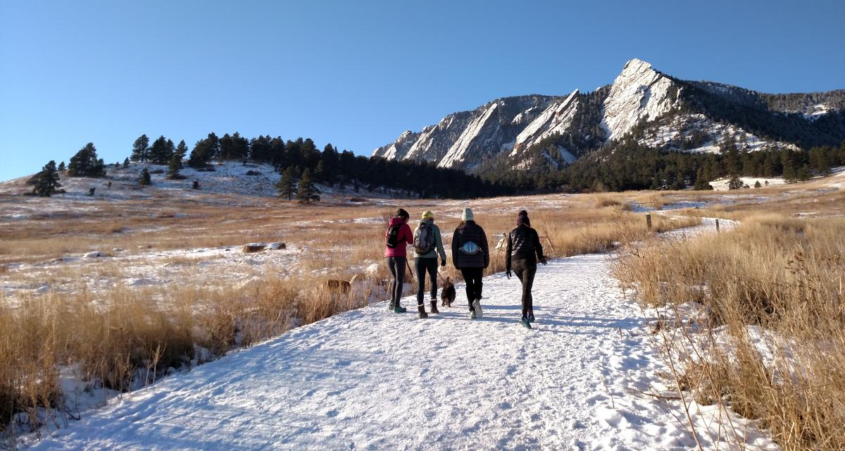 Group of four women with a dog hiking Chautauqua with the Flatirons in the winter