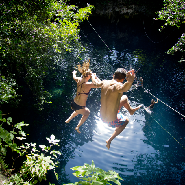 People Jumping into Cenote Pool