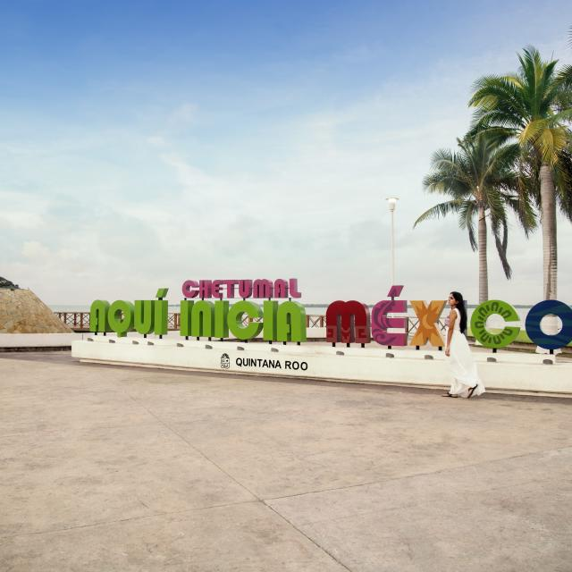 Woman In White Dress Walking Past Chetumal Novi Inicia Mexico Sign
