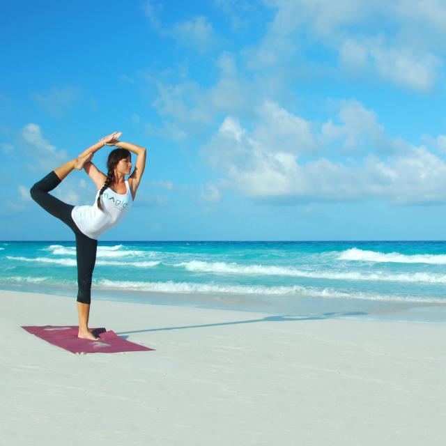Woman Doing Yoga on Beach