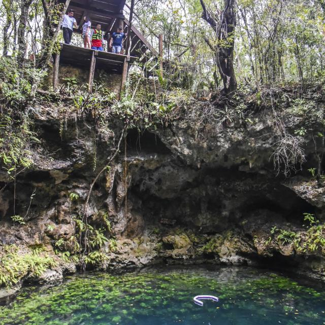 People Looking Down into Cenote with Divers