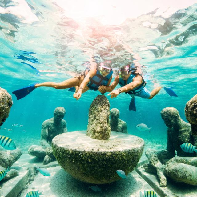 Snorkelers looking at underwater sculptures