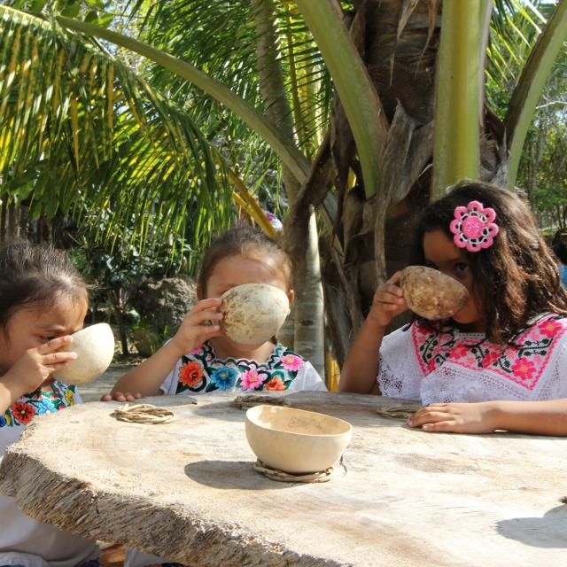 Children at Table Sipping from Bowls